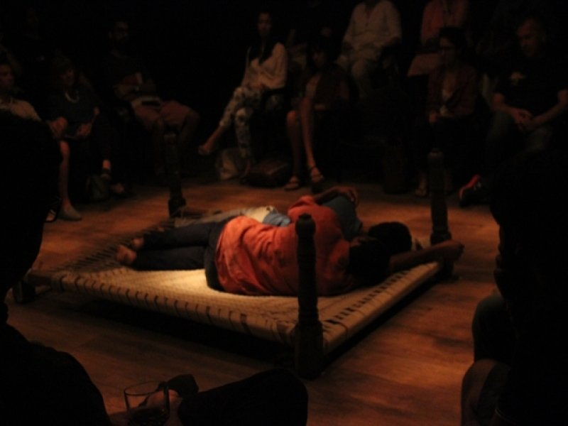 This seventh photograph shows 'Queen-size' being performed at the OddBird Theatre in Delhi. In this photograph, the charpoy is at its usual central position in the performance space, but is turned upside down. Both dancers seem to be asleep on the charpoy, with Lalit Khatana snuggling up to Parinay Mehra from behind, his left arm on the left shoulder of Parinay Mehra and right hand stretched out towards the edge of the charpoy. They have their backs to the camera. They are in their usual attire – grey t-shirt and cream coloured trousers for Parinay Mehra, and orange shirt and dark trousers for Lalit Khatana. Light from the arrangement above seems to fall gently on them and the wooden floor around the charpoy. At least a dozen people are visible in muted light, seated all around the performance space. Photo credit: Sidharth Sarcar.