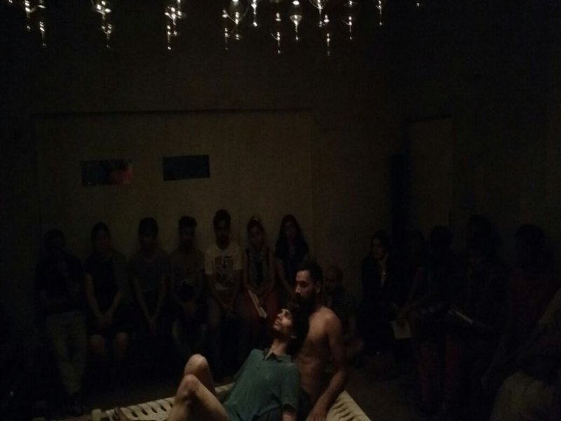 This eighth photograph shows a scene from the 'Queen-size' premiere at Jor Bagh in Delhi. The camera is quite up close to the two performers – Lalit Khatana is bare-chested, half seated, reclining on his elbows in one corner of the charpoy; Parinay Mehra with bare legs and grey-green t-shirt is lying on his back on Lalit Khatana, with his head on Lalit Khatana's chest. Both dancers have their eye closed. The lights above, only partially visible, seem to be swaying lightly. Around 15 viewers are visible in muted light in the background – on two sides of the charpoy – watching intently. The wall on one side of the performance space has two rectangular cutouts, possibly for the purpose of projection. Some people seem to be peering in through these cutouts as well. Photo credit: Virkein Dhar.