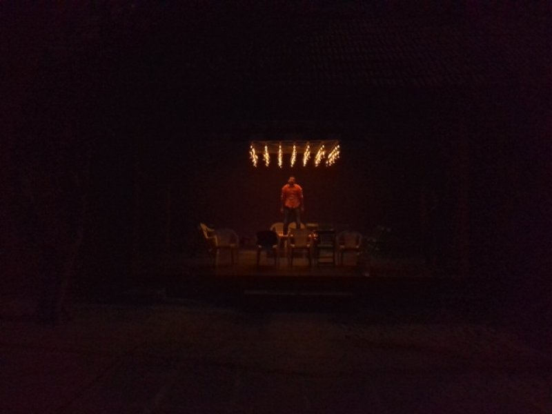 This ninth photograph is taken outdoors in the evening darkness at SPACES, Chennai, a pioneering contemporary dance institution in India. The photograph is a long shot of the performance space for 'Queen-size' – a large, shed-like open structure with a slanted and tiled roof and a raised two-step high platform. The show is yet to start and only dancer Lalit Khatana can be seen standing on the charpoy in the centre, posing for the photograph with a smile. There are empty chairs all around the charpoy. The only light source is the gleaming light piece, all lamps ablaze, not far above the tall dancer's head. Everything else is shrouded in darkness. Only the trunk of a tree to the left of the shed is barely visible, as is a part of the courtyard floor where the shed stands. Photo credit: Mandeep Raikhy.