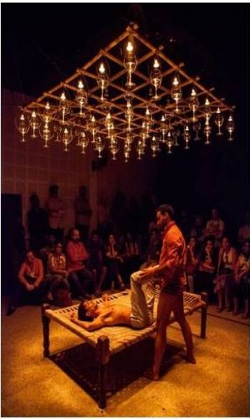 This fourth photograph shows 'Queen-size' being performed at the Attakkalari Biennial in Bangalore. It provides a clear view of Parinay Mehra on his back on the charpoy; his legs raised and folded at the knees, the lower halves held by Lalit Khatana, who is standing upright next to the charpoy. Parinay Mehra is wearing only cream coloured trousers, while Lalit Khatana is in an orange shirt with folded sleeves and in red and black horizontally-striped underwear. Jonathan O' Hear's light piece gleams splendidly against the dark ceiling above and throws a golden glow on the charpoy and the performers below. About two dozen viewers in rapt attention are seated on the far side of the performance space around two sides of the charpoy. Photo credit: Magali Couffon.