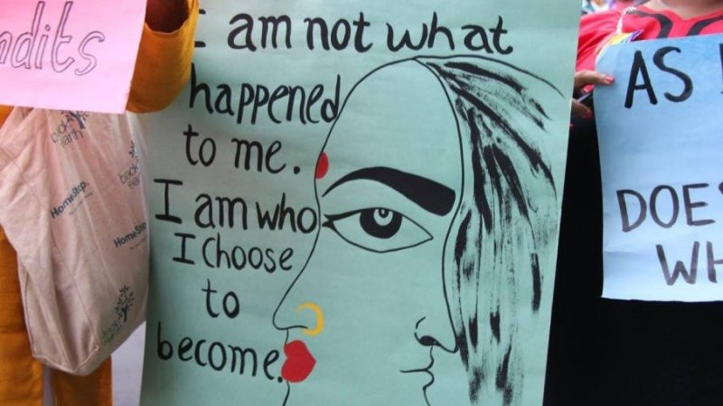 "The photograph shows a close up shot of a poster with a message on gender diversity and equity at the 'Kolkata Rainbow Pride Walk' held on December 11, 2016. The message says ""I am not what happened to me. I am who I choose to become."" The text is accompanied by the drawing of a double-face – the masculine and the feminine elements mirrored in a single human face. The feminine elements have been symbolized by a red 'bindi', red lips and a golden nose bangle. The person carrying the poster is not visible. There are other people around carrying more posters. Photo credit: 'Hidden Pockets'."