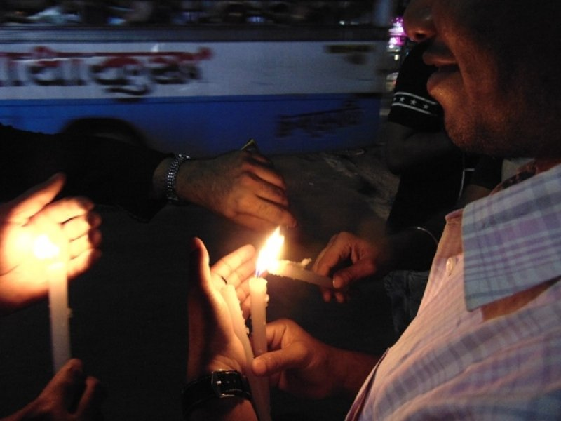 This photograph is also from the 'MyNameKeepsChanging – No More Rape, Murder and Violence' event organized by Maitree at Hazra Park in South Kolkata on April 18, 2018. The photograph has been taken after dark and shows a close-up of a number of people lighting candles from each other – only their forearms, hands and wrist watches visible in the picture. The smiling side face and shirt collar of one of the persons is also partially visible as he holds a candle from which most others are borrowing the light. In the background can be seen the blur of a public bus passing by, and some lights from across the road. Photo credit: Pawan Dhall