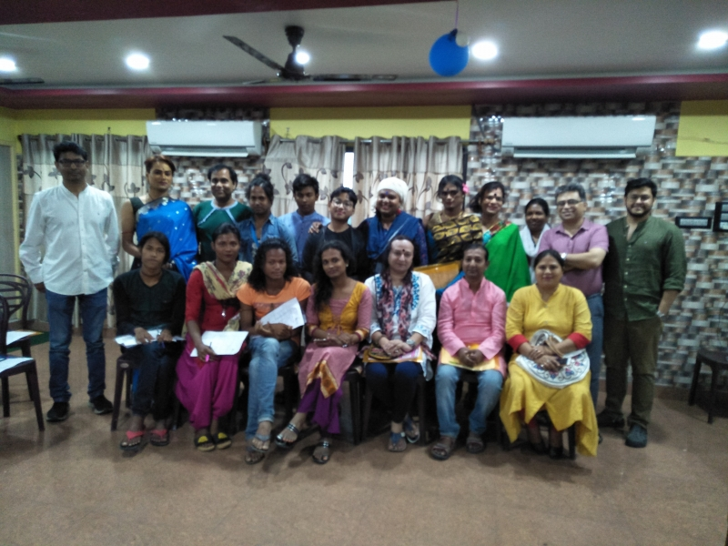 This is a group photograph of 19 participants at an introductory event for the Varta Trust Legal Aid Support Group Project held at Maa Basanti Lodge, Islmapur on April 27, 2019. The event was a North Bengal launch of the project and the participants included representatives of queer community groups from different districts of North Bengal, queer friendly lawyers, members of the queer communities from Islampur town and its neighbourhood, and members of the project team who had travelled over from Kolkata. The photograph shows the participants in two rows, people in the front row sitting on chairs, the others standing behind them. The photograph is taken inside the conference room at the event venue. Photo credit: Anonymous