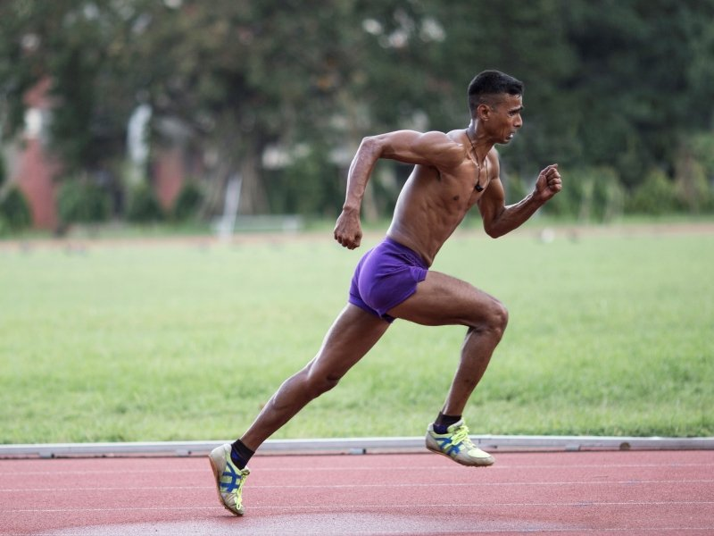 This is also a photograph from the 'Verve' calendar – it shows a male para-athlete running on a synthetic track. He has a muscular but lean frame, is about 6 feet tall, has short cropped hair, is wearing purple shorts, running shoes and an amulet around his neck. Photo credit: Archan Mukherjee