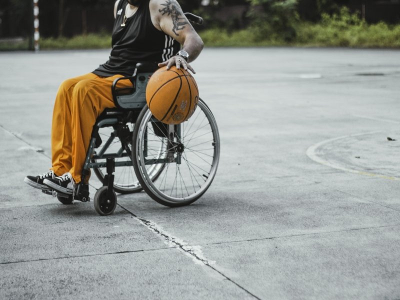 Another photograph from the 'Verve' calendar – it shows a basketball player in a wheel chair on an outdoor concrete ground. He is bouncing the ball with his left hand, and with the other, not visible, is possibly navigating the movement of the wheel chair. He is wearing a black singlet, orange track pants, white and black sports shoes, and a clunky watch on his left wrist. He has a huge centaur tattooed on his left upper arm. Photo credit: Sourav Chakraborty