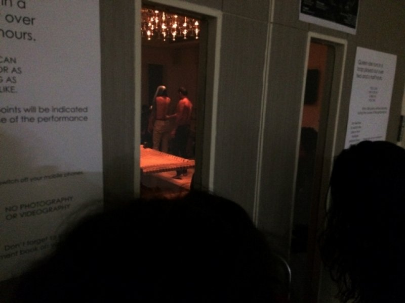This third photograph shows a glimpse of 'Queen-size' being performed inside a room at the Ashoka University in Sonepat. The doorway to the performance space is closed but it has glass panes through which two individuals are peering in. Both performers are standing next to the charpoy facing away from the camera – Parinay Mehra has his back to Lalit Khatana, with his grey t-shirt pulled up to his head. He is wearing cream coloured trousers. Lalit Khatana, in dark trousers, is also shirtless, and is right behind Parinay Mehra touching his back. Only one corner of the charpoy (which is between the doorway and the performers) and a part of the light piece on the ceiling are visible. The performance space, as usual, is bathed in a dim, warm light. On the outside, next to the glass panes are poster-size notices providing details of 'Queen-size' and dos and don'ts for viewers. Photo credit: Sidharth Sarcar.