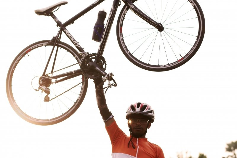 This is a photograph from the 'Verve' calendar – it shows a male cyclist smiling and holding aloft above his head a Ridley bicycle with his right hand. He is holding the bicycle at the pedals joint. He is in full cycling gear, with a helmet and arm sleeves, and is wearing an orange tee. We can see only the upper half of his body, chest onwards, almost as if he was airborne. He is in an outdoor location. The photograph is taken early evening, against the sunlight, which is shining through the left wheel and adding to the airborne effect. Photo credit: Souvik Banerjee