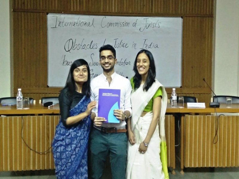 This is a photograph of the researchers and authors of the report – lawyer Danish Sheikh is standing in the centre displaying a copy of the report; to his right is social researcher Ajita Banerjie and to his left is lawyer Sanhita Ambast. All three are smiling brightly. They are inside the conference room in India International Centre where the report was launched. We can see a whiteboard in the background with the title of the report written on it. The seating arrangement for the panel discussion speakers is also visible behind the three persons. Photo credit: International Commission of Jurists
