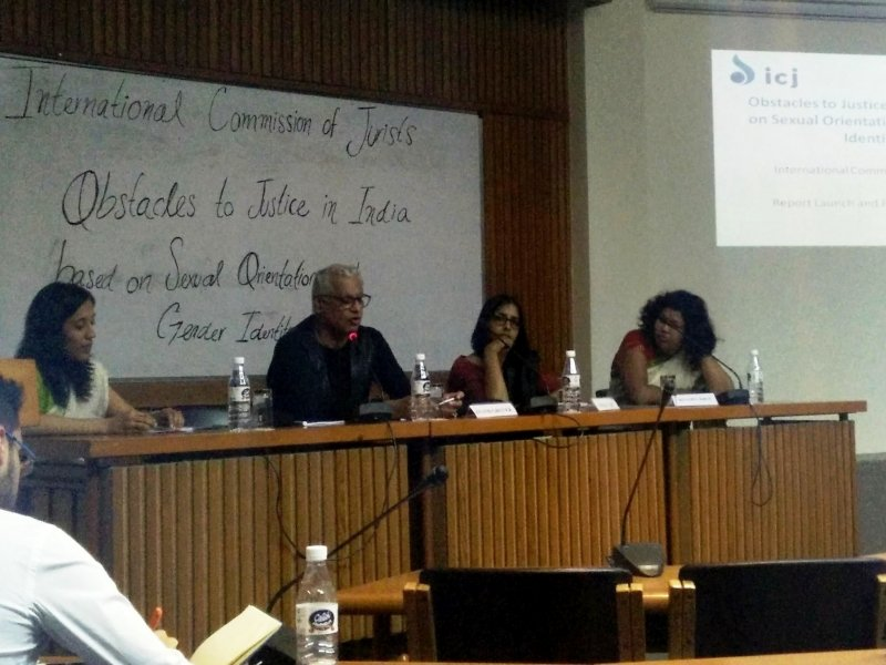 The photograph shows the panel discussion mentioned in the report in progress. Seated from left to right are: Report co-author Sanhita Ambast, senior advocate Anand Grover, academic Dipika Jain, and queer activist Rituparna Borah. Anand Grover is speaking while the others look on. There is a whiteboard in the background with the title of the report written on it. To the right side of the whiteboard is a screen projecting the title of the report. In the foreground are chairs for the audience. It is a close shot of the panellists, and so the audience is not visible. Photo credit: International Commission of Jurists