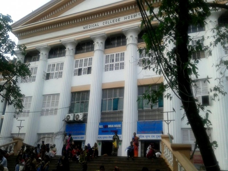 "Photograph shows scores of people sitting and waiting on the open stairs leading up to the Kolkata Medical College & Hospital building. A few are standing around. A blue, red and white signage on the entrance to the building says ""M. S. Life Drug House – Chemists & Druggists"". It also says (in Bengali) that this is a fair price medicine shop (similar signage on either side says the same thing in English and Hindi). It is a day time photograph. The building, built in a neo-classical style of architecture in the mid 19th century by the British, is painted in white with gold linings on the roof and elsewhere. In the foreground are a couple of trees. Photo credit: Dr. Shaoni Sanyal."