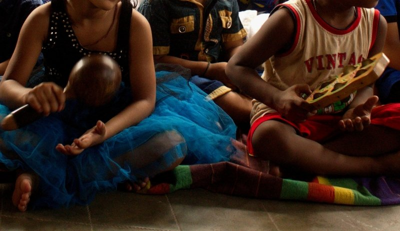 The photograph shows a close-up shot of the hands of two young children with autism. One of them is playing a rattle, the other a tambourine. The children are sitting cross-legged on the floor, and there are other children around them. We can't see the faces of the children as the focus is on their activities. The photograph was taken during an event organized on April 3, 2017 in Kolkata to mark Autism Awareness Day (which was on April 2). The event consisted of poetry recitals, songs, music, dance and storytelling involving a number of children with autism, their parents, guardians and caregivers. The event was organized by Transcendent Knowledge Society, an NGO that runs Wonder House, a day-care centre for children with autism in the Tollygunge area of Kolkata. Photo courtesy Transcendent Knowledge Society