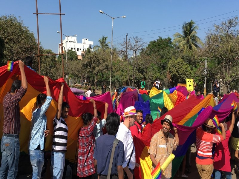 Photograph shows a scene from the 'Hyderabad HLGBTIQ Pride 2017'. The walkers (around 30 of them are visible in the photograph) are carrying aloft a huge rainbow flag stretching several metres – we can't see the entire flag in the photograph. It is made of silky cloth, which glistens in the bright sun. It seems to be the front end of the pride march, as it takes a turn from one road onto another. The walkers are all smiles and shouting slogans, with photographers trying to take shots from strategic angles. The colours of the rainbow flag seem to stand out against the green of the tree-lined roads and the bright blue of the sky. Photo credit: Dr. Mukut Bhowmik.