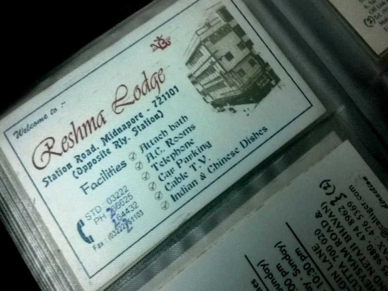 "This is a photograph of the visiting card of Reshma Lodge, located on Station Road in Midnapur town. The card says: ""Welcome to Reshma Lodge, Station Road, Midnapore - 721101, (Opposite Rly. Station)"". A list of facilities is also provided: ""Attach bath, AC rooms, telephone, car parking, cable TV, Indian and Chinese dishes"". Their phone and fax numbers are also provided: ""03222 266 625 and 264 432"" and ""03222 251 103"", respectively. A small black and white photograph of the hotel is provided to the right hand side of the card. The card is placed in a pocket made of transparent plastic in one of the visiting card diaries of the author. Photo credit: Pawan Dhall"