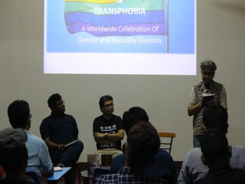 This second photograph from the event 'Books, Films and IDAHOBIT 2017' shows painter-graphic designer and event anchor Rudra Kishore Mandal introducing the two authors of the day Dr. Rohit K. Dasgupta and Pawan Dhall to the audience. The authors are seated on chairs facing the audience while the anchor is standing to their left, reading out from some papers in his hand. In the foreground we can see a few members of the audience, their faces turned towards the authors and the anchor. In the background is a screen projection of a graphic highlighting the International Day Against Homophobia, Biphobia and Transphobia. Photo credit: Arunabha Hazra