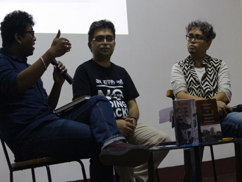 "This third photograph from the event 'Books, Films and IDAHOBIT 2017' shows a conversation in progress between the two authors of the day, Dr. Rohit K. Dasgupta and Pawan Dhall, and the event anchor Rudra Kishore Mandal. All three are seated on chairs facing the audience, with the two books launched are displayed on a small table in front of them. Dr. Rohit K. Dasgupta (first from the left) is speaking, holding a microphone in his left hand while gesturing with the right. Pawan Dhall (in the centre) and Rudra Kishore Mandal (third from left) look on as he speaks. Pawan Dhall is wearing a black t-shirt with the logo of the 'No Going Back 377' campaign emblazoned on it in white. A line in Hindi above the logo says ""Ab Wapsi Nahin"" (implying now there's no turning back in the struggle against Section 377 of the Indian Penal Code, which unjustly criminalizes queer people). Photo credit: Arunabha Hazra"