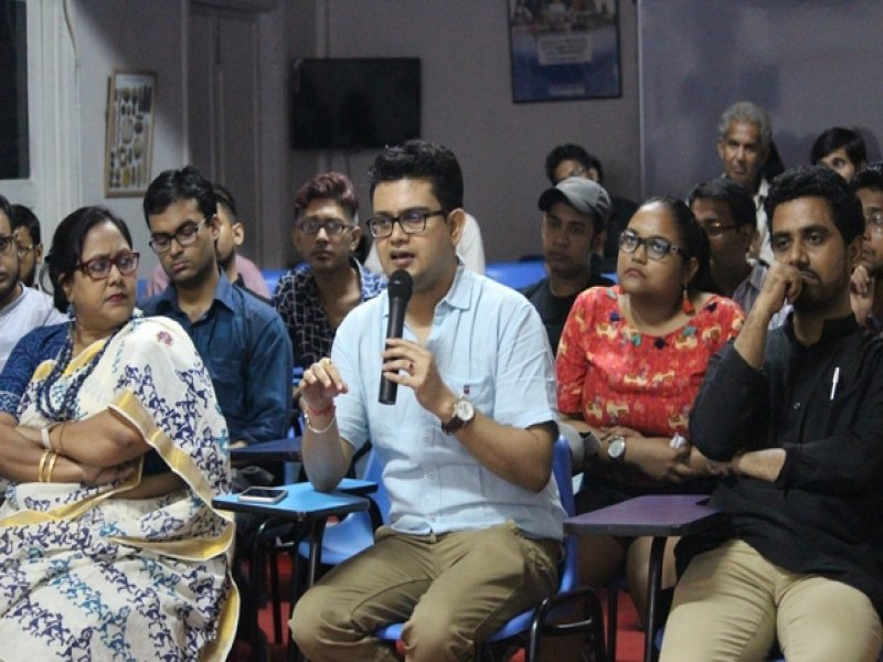 This fourth photograph from the event 'Books, Films and IDAHOBIT 2017' shows a member of the audience holding a microphone and asking a question during an interface with the two authors of the day Dr. Rohit K. Dasgupta and Pawan Dhall. The speaker is facing the camera and around 15 people (most of them men and a couple of women) are visible in the audience, seated around the speaker. Some of them seem to be listening intently to the speaker. Photo credit: Arunabha Hazra