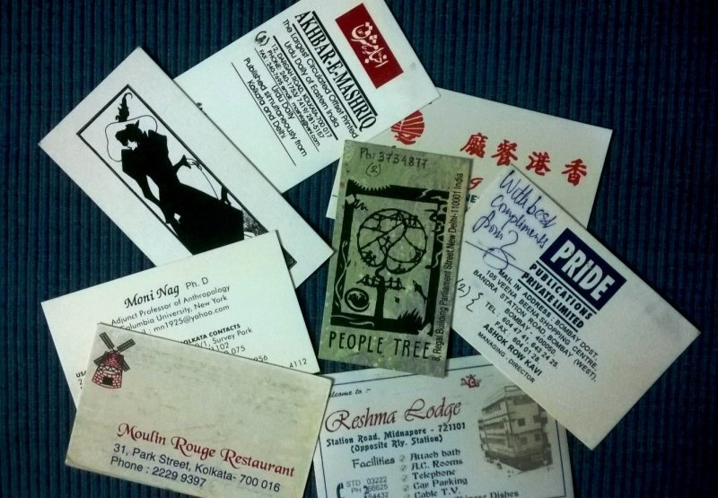 Photograph is a close-up shot of a number of visiting cards from the author's collection scattered on a surface. These are the cards of 'Akhbar-E-Mashriq', an Urdu daily newspaper published from Kolkata; late anthropologist Dr. Moni Nag; Moulin Rouge Restaurant, Park Street, Kolkata; People Tree, Parliament Street, Delhi; Pride Publications Private Limited, Bombay; and Reshma Lodge, Station Road, Midnapur. There are two other cards – one that shows a few Chinese alphabets (the rest of the details are hidden by the other cards); another unnamed card that shows a black and white sketch of a tall, slender and sharp-featured white woman dressed in Victorian style clothing, including a large hat. Some of the cards are on glossy paper, others on cardstock (thick) paper often used for business cards, and one is on handmade paper. Most cards are horizontal in orientation. Photo credit: Pawan Dhall