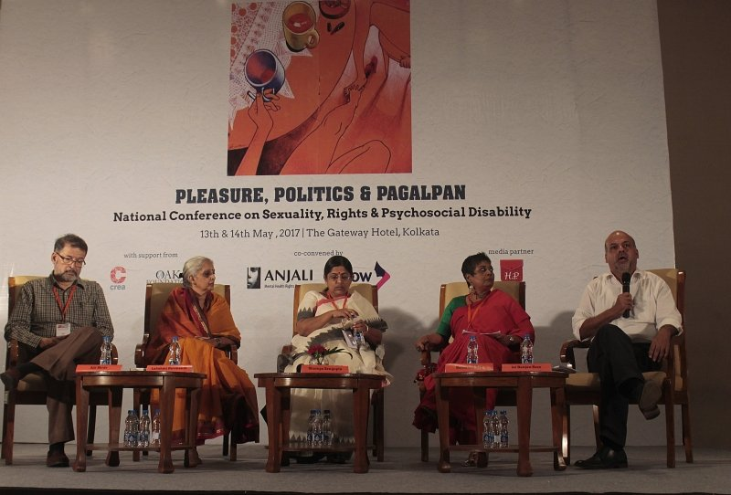 This photograph shows a panel discussion under way on the first day of 'Pleasure, Politics & Pagalpan – National Conference on Sexuality, Rights and Psychosocial Disability'. Seated on the dais (from left to right) are psychiatrist Dr. Ajit Bhide, psychologist Lakshmi Ravikanth, the author – disability rights activist Shampa Sengupta, mental health rights activist Ratnaboli Ray (also the founder of Anjali), and panel moderator Dr. Jai Ranjan Ram. The moderator is speaking with microphone in hand. Low tables with name cards and water bottles are placed in front of the speakers. In the background is a large floor-to-ceiling banner with the conference logo and name, and the names of the organizers printed on it. The conference was co-convened by Anjali Mental Health Rights Organisation, Kolkata and Arrow, Kuala Lumpur with support from CREA, Delhi; Oak Foundation, Kolkata; and media partner Hidden Pockets. It was held on May 13-14, 2017 at The Gateway Hotel in South Kolkata. Photo credit: Sagnik for Anjali.