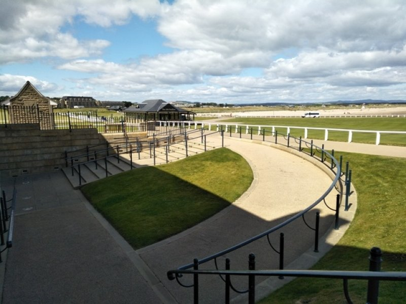 This is another daytime photograph of a portion of the golfing course in St. Andrews, which is about an hour by road from Dundee and located on the North Sea coast. Taken from the top of a path gently sloping towards the entrance of a club house, the photograph also shows a flight of stairs and a second gently sloping path from another direction leading to the same entrance. The stairs too seem easy to climb, and all the pathways and stairs have hand railings on the side. In the background are green expanses of the golf course, more club house like buildings, hilly areas and a clouded but bright skyline. St. Andrews is reputed for its university, some of the finest and oldest golfing courses in the world, as well as its castles, museums and sandy beaches. Photo credit: Pawan Dhall