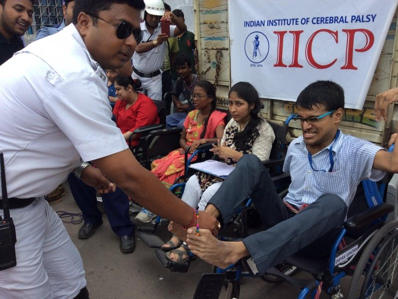 This second photograph is also from the event organized by the Indian Institute of Cerebral Palsy (IICP) outside the South City Mall in Kolkata on Raksha Bandhan this year (August 7, 2017). A young man with a disability in both his arms ties a 'rakhi' on the right wrist of a traffic police man with his feet. The police man bends forward and looks on appreciatively, as one of his colleagues takes a photograph from his mobile phone camera in the background. Three women with disabilities, all seated on wheel chairs, can also be seen next to the man tying the 'rakhi'. A number of IICP volunteers and other people can be seen moving around and cheering for the 'rakhi' ritual. Behind the wheelchairs is the backside of a truck on which a small IICP flex banner is displayed (the name of the organization and their logo is printed on the banner). Photo credit: Jeeja Ghosh Nag