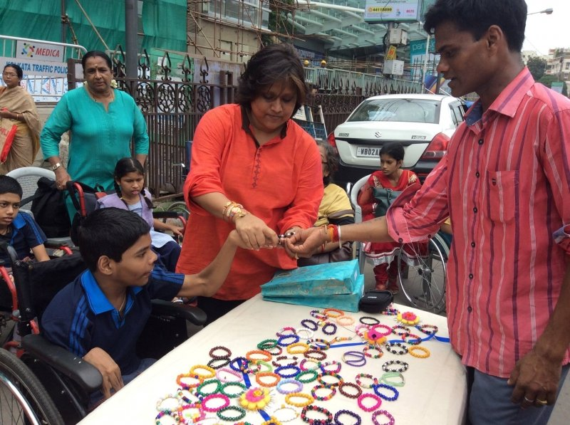 This main photograph shows an event organized by the Indian Institute of Cerebral Palsy (IICP) just outside the South City Mall in Kolkata on Rakshan Bandhan day this year (August 7, 2017). On a table several friendship bands made of colourful beads and some 'rakhis' are on display. To the left of the table is a disabled child seated on a wheel chair. An IICP volunteer is next to him, and helps him tie a 'rakhi' to a man (presumably a transport worker) standing to the right of the table. All three individuals are smiling. In the background more children with disabilities can be seen seated on wheel chairs, some with their guardians or companions. Other people can also be seen in the background, as also the pavement railings outside the mall, Kolkata Traffic Police signboards, some hoardings, a white car and a few buildings in the distance. Photo credit: Jeeja Ghosh Nag
