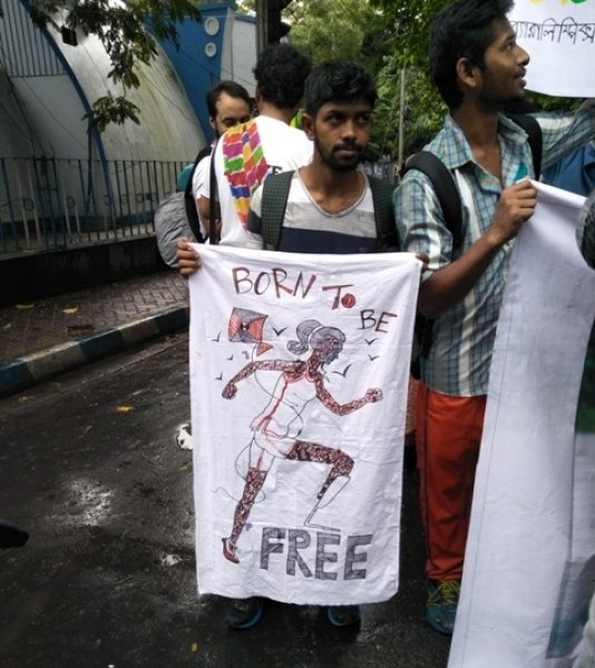 "This photograph shows a scene from NGO Civilian Welfare Foundation's annual walk in Kolkata to celebrate the cause of the Paralympics. A walker is seen standing with a poster that says ""Born to Be Free"" and has the sketch of a para-athlete in a running pose drawn in the centre. Birds can be seen flying in the background of the poster, as also a kite soaring in the sky. The text and the graphics are rendered in eye-catching red and black. A few other walkers can be seen next to the walker holding the poster. This year's walk in South Kolkata on August 28, 2017 attracted nearly 300 participants, including a number of para-athletes who won medals for India in the Paralympics held last year in Rio de Janeiro. Photo credit: Pawan Dhall."