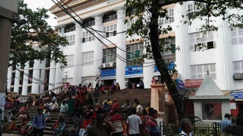 "Photograph shows scores of people sitting and waiting, mostly in small groups, on the open stairs leading up to the Kolkata Medical College & Hospital building. A few are walking up or down the stairs. A blue, red and white signage on the entrance to the building says ""M. S. Life Drug House – Chemists & Druggists"". It is day time, and many people are walking past the stairs to elsewhere in the hospital complex. The building, built in a neo-classical style of architecture in the mid 19th century by the British, is painted in white with gold linings on the roof and elsewhere. In the foreground are a couple of trees and a small temple to the right of the stairs. Photo credit: Dr. Shaoni Sanyal."