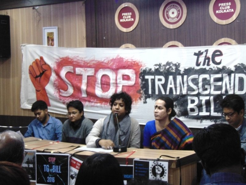 "The photograph shows a media conference in progress at the Kolkata Press Club on December 14, 2017 – the media interaction was called on the matter of the campaign against the Transgender Persons (Protection of Rights) Bill 2016. Transgender activist Anindya Hajra, sitting behind a panel discussion desk, can be seen addressing the media persons, with Hijra activist Aparna Banerjee and advocate Kaushik Gupta to their left and transgender activists Anush Dutta and Sampurn Ghosh to their right. A hand-painted banner can be seen in the background, which says ""Stop the Transgender Bill"" in large and bold text (which is partially hidden) and also has a pumped fist drawn next to the text. Above the banner can be seen the logos of Press Club Kolkata. A few posters on the campaign theme can be seen pasted on the front side of the panel desk facing the media persons. In the foreground can be seen a few people facing away from the camera, towards the speakers. Photo credit: Pawan Dhall"