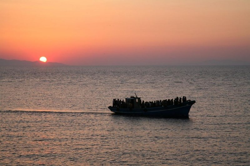 The photograph is an image from the 2009 film 'Eden Is West' ('Eden à l'ouest') directed by Greek-French filmmaker Costa Gavras. It is a long shot of a medium-sized motorized boat full of people standing or sitting on the edges, presumably undocumented immigrants. As the boat crosses a calm sea, it leaves behind a wake in the water. In the background the sky is aglow with the sun setting behind distant mountains. The entire scene is one of melancholy. The film 'Eden Is West' is a drama centred around the undocumented immigrants living in the European Union. The image has been used in a representational sense here. Photo courtesy: Google Images