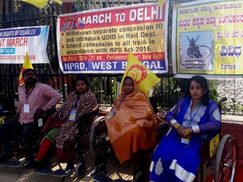 """This is a second photograph from the demonstration organized on Parliament Street, Delhi, March 6, 2018 morning. Four people (one man and three women) with disabilities can be seen seated on wheelchairs at the demonstration site, facing the camera. Behind them is a high railing with a number of banners on the subject matters of the demonstration put up on the railing. The banners are in different languages. The main one visible in the photograph says """"March to Delhi to: (a) Withdraw separate concession ID and introduce UDID in Rail Dept.; (b) Extend concession to all trains in accordance with RPD Act, 2016."""" Below the main lines are details of the demonstration: """"6th March, 2018, 11 am, Parliament Street, New Delhi"""". At the bottom is the name of NPRD, West Bengal. Yellow flags of the Paschimbanga Rajya Pratibandhi Sammilani are also visible in the photograph. Photo credit: Shampa Sengupta"""