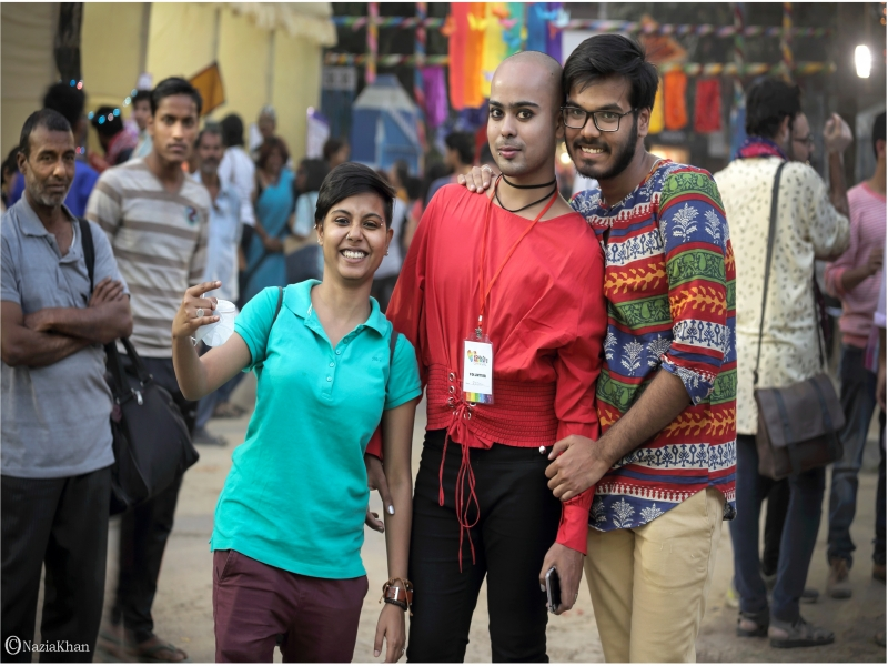 This photograph captures a happy and 'genderqueer' moment from the 'Kolkata Rainbow Carnival 2018'. Three individuals, all smiles, are posing for a photograph. From the looks of it these individuals include one female and two males, but we don't know how they self identify in terms of gender. Besides, all are dressed in a manner that could be considered gender non-normative – in terms of the dress items, colours and cuts of the clothes, and accessories. One of the three individuals, who has a distinctly androgynous appearance, is wearing the tag of a carnival volunteer on their neck. A couple of men look on at the three individuals, standing a little distance behind them. In the background are many people standing around, chatting and visiting the stalls displaying clothes and craftwork. The carnival was organized by the West Bengal Forum for Gender and Sexual Minority Rights on February 18, 2018 at Triangular Park in South Kolkata. Photo credit: Nazia Khan