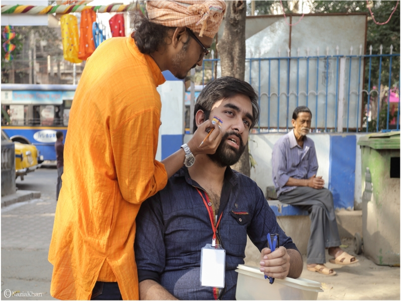 This photograph from the 'Kolkata Rainbow Carnival 2018' shows a young hirsute man in fitting clothes getting his face painted by a make-up artist. The young man, with a carnival volunteer tag on his neck and a pair of spectacles in his left hand, is seated on a chair, while the artist stands next to him and peers over him to paint a rainbow flag on his right cheek. The artist is also tastefully dressed in a 'kurta', jeans, spectacles, turban and a clunky wristwatch. An aged man can be seen in the background, seated on a bench under a tree, looking at the two men. The face painting stall is near the entrance of the park where the carnival was held. In the background one can see decorations hanging above the entrance, traffic outside on the road, a portion of the park railing, and the back of a billboard put up against the railing, blocking the view of the pavement on the other side. The carnival was organized by the West Bengal Forum for Gender and Sexual Minority Rights on February 18, 2018 at Triangular Park in South Kolkata. Photo credit: Nazia Khan