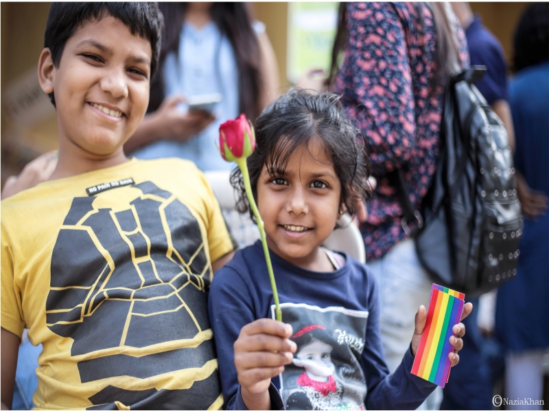 This last photograph is yet another cheerful moment from the 'Kolkata Rainbow Carnival 2018' – it is a close-up shot of two children, a boy and a girl, with bright smiles facing the camera. The girl is holding up a long-stemmed red rose in one hand and a few small rainbow flag stickers in the other. Both the children are dressed in t-shirts. The blurred background of the photograph shows a number of people hanging around, chatting and enjoying the carnival, which was organized by the West Bengal Forum for Gender and Sexual Minority Rights on February 18, 2018 at Triangular Park in South Kolkata. Photo credit: Nazia Khan
