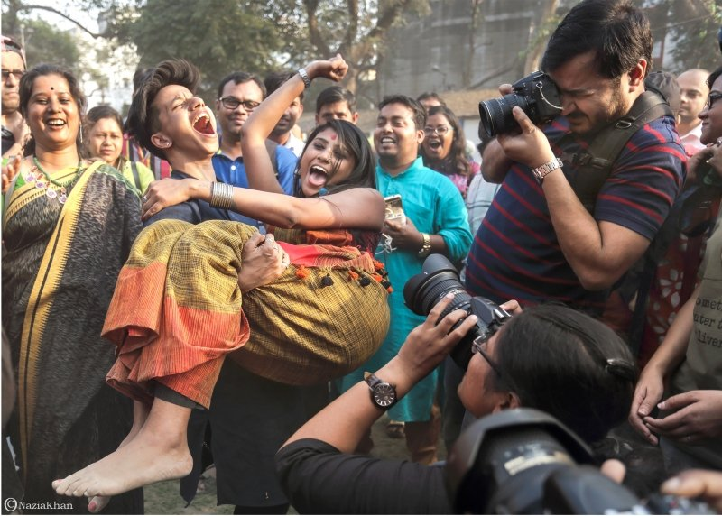 This photograph captures a boisterously happy moment from the 'Kolkata Rainbow Carnival 2018'. A woman exults in joy as she picks up another woman in her arms, quite clearly heavier than herself. The second woman is also all laughter and pumps her fist in the air at the success of her friend. A crowd of people around the two women also laughs and cheers, as a number of photographers mill around to capture the moment. The woman doing the lifting is dressed in a 'kurta', has short cropped hair and tops in her ears. The woman being lifted is dressed in a colourful saree and 'bindi'. The carnival was organized by the West Bengal Forum for Gender and Sexual Minority Rights on February 18, 2018 at Triangular Park in South Kolkata. Photo credit: Nazia Khan
