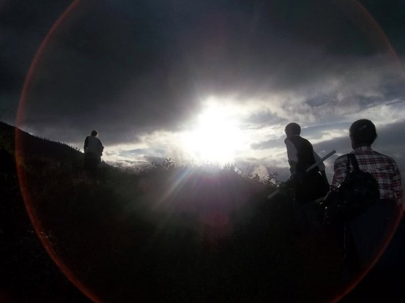 This photograph is symbolic in relation to the article to which it is associated. It shows the light of the sun, occupying the centre of the top half of the photograph, spread across the horizon past a hill. The sunlight dazzles through a break in dark clouds spread across the sky. Two persons (gender indeterminate) to the right side of the picture climb the hill, one behind the other, while a third person (gender indeterminate again) is on the left, higher up on the hill and much ahead of the other two. The sunlight and the peak of the hill, covered with small shrubs and grasses, seem to collide with each other. One of the persons on the right side, the one climbing ahead of the two, has a white shirt and dark sweater on and carries a long roll of paper in their left hand and a bag slung on their left shoulder. The person behind them wears a chequered shirt and carries a black bag on their left shoulder. A giant red halo formed by the sunlight playing against the camera lens encircles the three individuals in the picture. The photograph seems to convey a sense of an 'uphill battle', something that characterizes the struggles of the Indian queer movement as well. The dazzling sun in the horizon, the light of knowledge and liberty, beckons. Photo credit: Hari Chettri