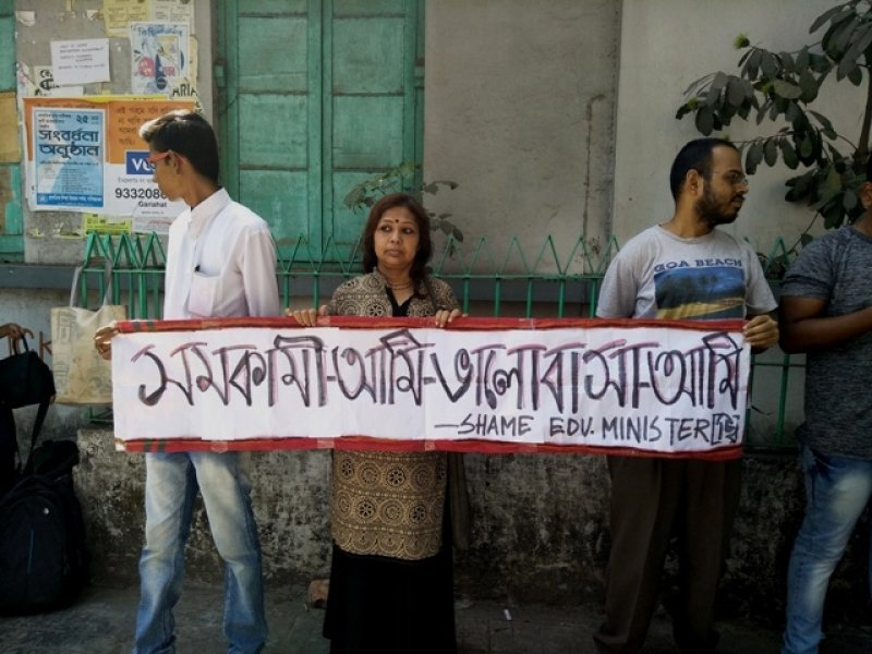 """Another scene from the gathering of people on the pavement outside Kamala Girls' High School in South Kolkata to protest the incidents in the school and the West Bengal Education Minister's comments on the matter. The time would be around midday on March 19, 2018. Three individuals can be seen holding a placard that says in part Bengali, part English: """"Samakami aami, bhalobasha aami. Shame Education Minister!"""" (So what if I'm homosexual, my love has meaning. Shame Education Minister!) Behind the protestors is the school building wall, with a closed window. Torn and peeling posters take up one part of the wall to the left. Shoulder bags of some of the protestors can be seen lying on the ground to the left. There are a couple of small plants behind the protestors, growing in a small enclosure running parallel to the school wall. Photo credit: Pawan Dhall"""