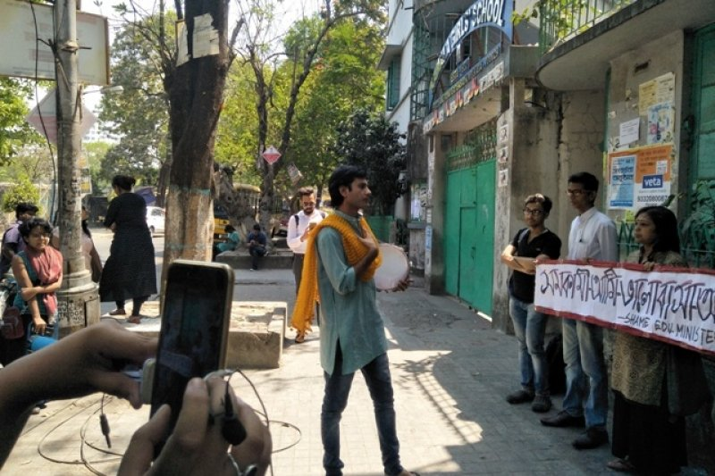 "In this photograph, a midday event is taking place on the pavement outside Kamala Girls' High School in South Kolkata on March 19, 2018 to protest the incidents in the school and the West Bengal Education Minister's comments on the matter. A street play is in progress. The main actor dressed in a 'kurta', pair of jeans, slippers and a 'dupatta' can be seen holding a tambourine in their hands and addressing the audience. About a dozen people, standing around at some distance from the actor, are watching. To the right of the photograph, facing the actor, are two individuals holding a placard in part Bengali, part English: ""Samakami aami, bhalobasha aami. Shame Education Minister!"" (So what if I'm homosexual, my love has meaning. Shame Education Minister!). Behind the placard holders is the school building and a part of the closed school gate can also be seen. The name of the school is written on an arched board above the gate. In the forefront, the photograph shows someone holding a mobile phone and recording a video of the play. Large trees, school buses, people sitting on platforms under the trees, and a building adjacent to the school make up the background. Photo credit: Pawan Dhall"