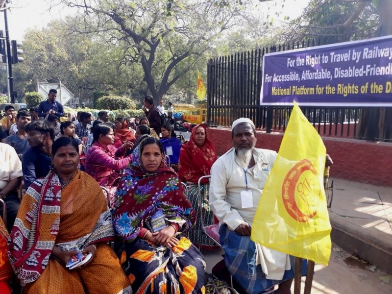 "The photograph shows a scene from a demonstration organized by disability rights groups from across India on Parliament Street, Delhi, March 6, 2018 morning to demand the right to travel by railways – in terms of both accessibility and affordability. The photograph captures just a small section of the people gathered at the demonstration. Around 25 people (a mix of men and women) can be seen seated on chairs or standing in a portion of the demonstration site, facing the camera. In the very first row are two women and a man, who is propping up a yellow flag of the Paschimbanga Rajya Pratibandhi Sammilani. To the right of the photograph, a banner can be seen put up on a high railing along the pavement. The banner has three lines saying: ""For the Right to Travel by Railways – For Accessible, Affordable, Disabled-friendly Railways – National Platform for the Rights of the Disabled"". In the background can be seen a few traffic barricades, a traffic signal, and several shrubs and trees. Photo credit: Shampa Sengupta"