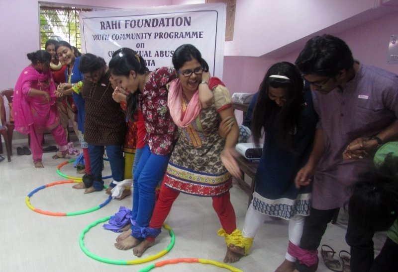 "The photograph shows a game in progress as part of a child sexual abuse awareness generation workshop organized by RAHI Foundation at Rabindra Bharati University, Kolkata in 2015. The participants, around 10 in number, are all older adolescents or young adults (most of them young women). The venue is an indoor one. The game seems to be focussed on team work and coordination. The participants, standing side-by-side in a long chain, are barefoot and have their ankles tied to the person next to them on either side with pieces of cloth. With hands held or placed over each other's shoulders, they are required to step forward together into hooplas placed on the floor. The participants seem to be all cheerful and having good fun in the process. Behind the participants is a banner that says ""RAHI Foundation Youth Community Programme on Child Sexual Abuse, Kolkata"