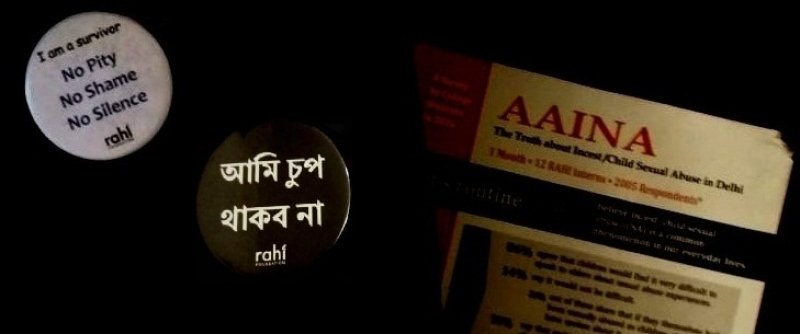 "This photograph shows a collection of RAHI Foundation's communication material on child sexual abuse. It shows two round badges with messages that say ""I am a survivor – no pity, no shame, no silence"" (in English) and ""Aami chuup thakbo na"" (in Bengali, which means 'I won't stay silent'). Both badges also have the logo of RAHI Foundation below the messages. A portion of a report brought out by RAHI Foundation with the title 'Aaina: The Truth about Incest / Child Sexual Abuse in Delhi' is also visible. But the focus is on the title with the rest of the text blurred out. The photograph has been modified such that the text on the material stands out in bright colours against a black background. Photo credit: Soma Roy Karmakar"