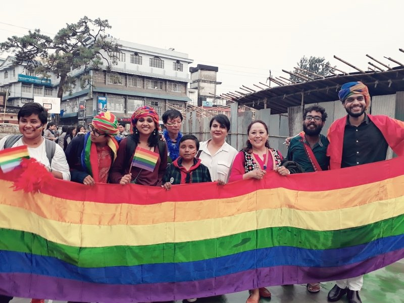 This photograph shows a scene from the starting point of the first 'Shillong Pride Walk' organized on September 14, 2018. The walk started at Fire Brigade Point. In the photograph, nine walk participants can be seen standing in a row, cheering and holding a large and flowing rainbow pride flag in front of them. The participants seem to be a mix of different genders. Some of them have smaller rainbow pride paper flags in their hands, while some are sporting colourful headgear. Among the participants are the author Shivalal Gautam at the extreme right end and advocate and Shamakami NGO founder Rebina Subba third from right. The participants seem to be standing in an open area and behind them can be seen some buildings, trees, a partition created by asbestos sheets and a tent like structure behind the partition. The sky above is grey and somewhat overcast. Photo courtesy: 'Shillong Pride Walk' organizers