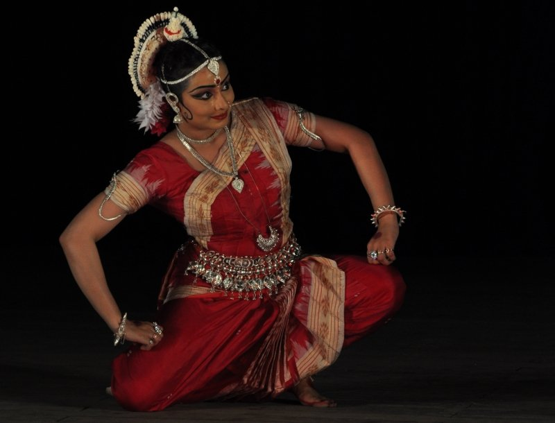 This photograph shows the author on stage enacting an Odissi 'abhinaya' to a popular song 'To Lagi Gopa Danda'. She is in a kneeling posture with the right knee touching the floor and the other folded ('abhanga' posture); she has her arms in a wide open stance with hands placed squarely on the knees and torso tilted to the right; her gaze is fixated to her left, away from the camera. Against a dark stage background, she looks resplendent in a deep red saree, silver ornaments and headgear traditional to the Odissi dance form. With eyes highlighted strikingly with kohl, she has a bright smile as she performs the act with grace. Photo credit: Kaushik Mukherjee