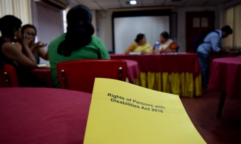 This photograph shows a copy of the Rights of Persons with Disabilities Act, 2016 lying in the foreground on a table. The name of the Act can be read on the cover, yellow in colour. In the background, the meeting room can be seen. To the left there are three people seated on chairs and engaged in a discussion; further beyond to the right is a person slightly bent over a table, writing something; and to his left are the two speakers of the meeting Dr. Rukmini Sen (Assistant Professor, Ambedkar University Delhi) and Shampa Sengupta (founder of Sruti Disability Rights Centre) – they are seated behind a long table meant for presenters and are facing the rest of the room. Behind them a white screen can be seen. The photograph is taken such that there is a sharp focus on the copy of the Act, while the rest of the photograph is relatively diffused. Photo credit: Abhirupa Kar