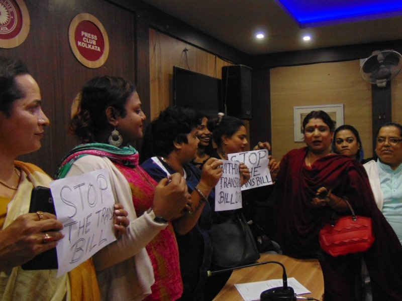 """This is a long shot of transgender activists and other community members from different backgrounds gathered at the Kolkata Press Club on December 20, 2018 to protest against the Transgender Persons (Protection of Rights) Bill, 2018. Eight individuals can be seen in the photograph, one of them a transgender man and most others either Hijra community leaders or other transgender women. Some of them are holding up banners that say """"Withdraw Transgender Bill 2018"""" and """"Stop the Trans Bill"""". Many are smiling at a quip made by one of the activists, while some others have a grim look. The photograph shows a good example of community solidarity. The Kolkata Press Club logo and a circular plaque with the club name can be seen mounted on the wall behind the activists. Other conference room equipment (a television and sound speaker) can also be seen in the background. Photo credit: Pawan Dhall"""