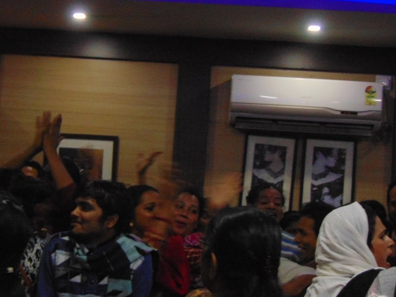 This photograph was taken at the end of the media conference at the Kolkata Press Club on December 20, 2018 to protest against the Transgender Persons (Protection of Rights) Bill, 2018. As the audience dispersed and left the conference room, many of the transgender individuals and their allies started an impromptu protest by clapping and jeering against the central government. The photograph shows many hands raised for clapping in the style (called 'theekri') deployed by Hijras and other transgender women. There are many smiling faces as the slogans are being shouted out. Some of the hands and faces are blurred because of the movement and general melee. The protest was serious but also good natured. In the background can be seen some framed artworks and an air-conditioner mounted on the wall of the conference room. Photo credit: Pawan Dhall