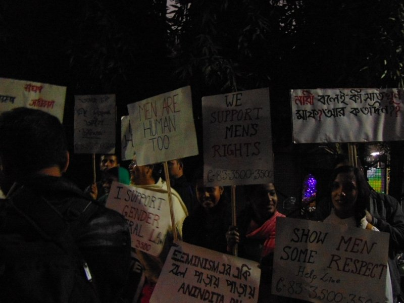 """This photograph shows a silent protest just outside the Kolkata Press Club organized by a men's rights group. This protest was not connected to the media conference on the Transgender Persons (Protection of Rights) Bill, 2018. It was related to a possible murder of a Calcutta High Court lawyer by his wife, also a lawyer, which was reported in Kolkata newspapers earlier in December 2018. Many of the protestors carried banners with messages like """"Men are human too"""", """"We support men's rights"""", """"Show men some respect"""", """"I support gender neutral law"""", and """"Nari bolei ki saat khun maaf? Aar katodin?"""" (Why should a woman allowed to get away with seven murders, how much longer will this go on?). The protestors included both men and women. The photograph was taken late in the evening under the light of street lamps interspersed with shadows cast by the trees around. Photo credit: Pawan Dhall"""
