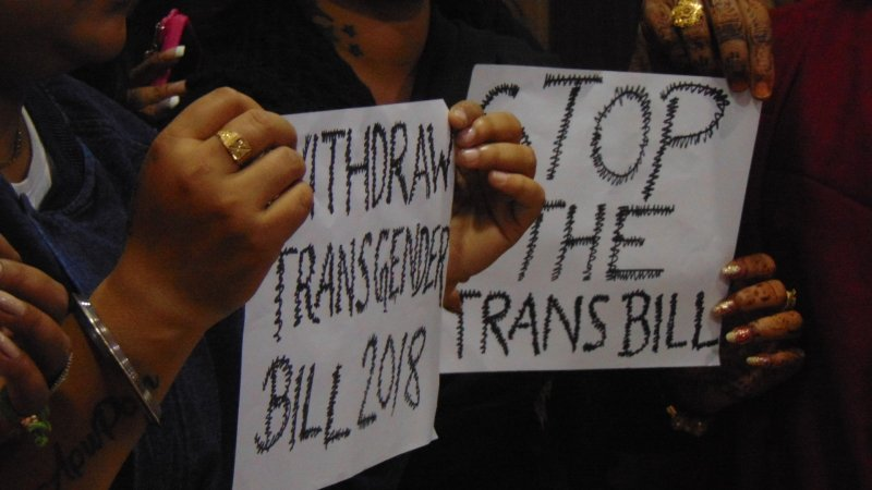 "This main photograph is a close-up shot of two small paper banners held up by transgender activists at a media conference organized at the Kolkata Press Club on December 20, 2018 to protest against the Transgender Persons (Protection of Rights) Bill, 2018. The banners say ""Withdraw Transgender Bill 2018"" and ""Stop the Trans Bill"". The hands and fingers of the persons holding up the banners can also be seen, some decorated with henna and nail polish and others ornamented with rings and bangles. Photo credit: Pawan Dhall"