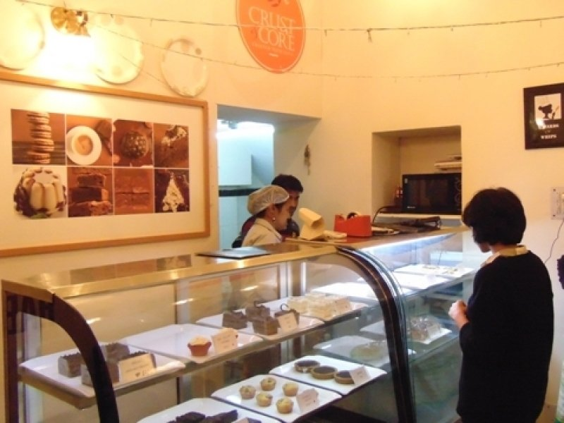 This photograph is focussed on the Crust & Core café counter. Several of the food items – desserts, savouries and breads are on display, kept in trays inside two large glass enclosures. Two staff members can be seen busy behind the counter, serving a customer standing in front of the counter with their back to the camera. One of the staff members, a woman who is likely the chef, has her hair covered in a white stretchable cap. A food packet and a tape dispenser are kept on the counter. A large framed picture of baked goodies occupies the wall behind the counter, bathed in golden colour from the lights above. Three large circular and decorative trays are fixed on to the wall in a row right above the picture. A little above the picture, to the right, is a large display of the Crust & Core logo. Almost right behind the staff members, the entrance to the kitchen is partially visible. To the left of the staff members, a microwave oven is kept on a shelf in the wall just next to the counter. Photo credit: Rith Das