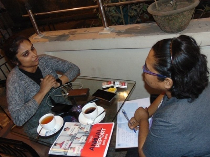 This photograph shows the author of this article Jia Mata in conversation with Rinku Soni, Assistant Secretary, Iswar Sankalpa at the café. They are seated at a glass-topped table with cups of coffee and tea in a small open space just outside the café near its entrance. The lights at the entrance light up the seating space in this late evening shot. Mobile phones of the two individuals can be seen kept on the table, as also a copy of the Annual Report of Iswar Sankalpa and two packets of cigarettes and a match box that belong to the author. She also has a pen and note pad open on her lap. Next to where the two people are seated is a small wall with potted plants and an iron railing, beyond which one can get a glimpse of the street on which the café is located. Photo credit: Rith Das