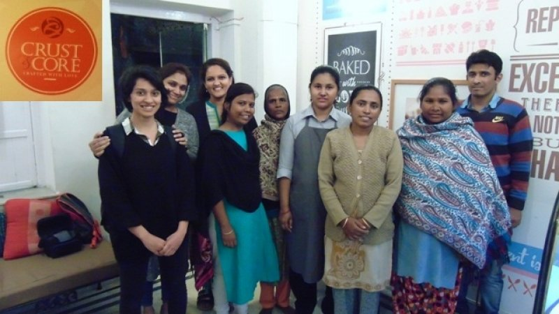 "This is a group photograph of some of the team members of Crust & Core café and bakery, which is the subject matter of this article. The photograph shows nine people standing in a row inside the café and smiling at the camera. The group includes some of the women survivors of mental illness and homelessness who are supported by NGO Iswar Sankalpa through training in baking, catering and running the café. The group also includes a couple of volunteers with the NGO, one male staff member of the café, and one member from the café management (Rinku Soni, Assistant Secretary, Iswar Sankalpa). Behind the team members, we can see the entrance to the café and some of the decorations on the walls of the café. To the right of the group of people in the photograph is a settee with a cushion, a small bag and a camera cover kept on it. The café logo is included in an inset on the top left corner of the photograph – the logo text says ""Crust & Core – Crafted with Love"". Photo credit: Rith Das"